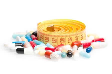 måttband med piller för diet runt på en vit bakgrund
