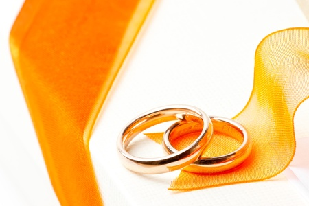 gold wedding rings near orange ribbon on white background photo