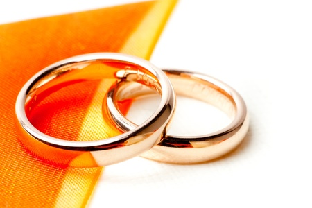 detail of gold wedding rings near orange ribbon photo