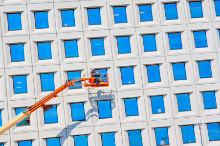 worker cleaning high tower with blue glass photo