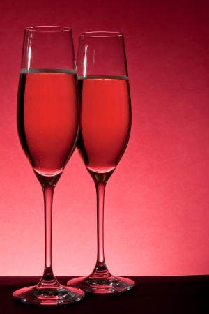 two full glasses of champagne over red background photo