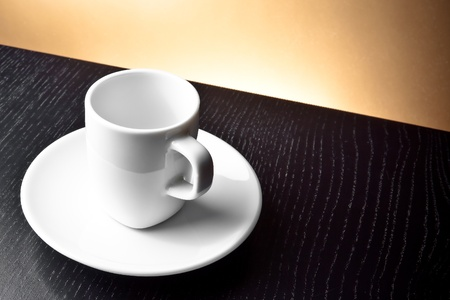empty cup on the wooden table and golden background Stock Photo - 21945805