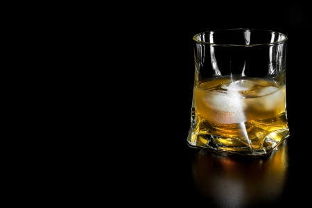 glass of whiskey with ice  with space for text on black background photo