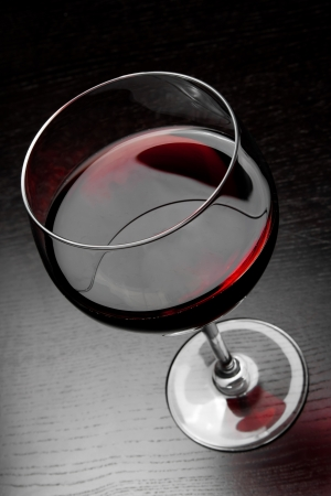 top of view of red wine glass on black wood table photo