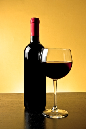 red wine glass near bottle on golden background and wood table photo
