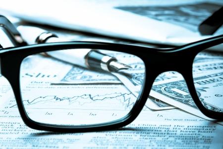 fondos negocios: cuadro financiero cerca de dólares visto por vasos desenfocados Foto de archivo