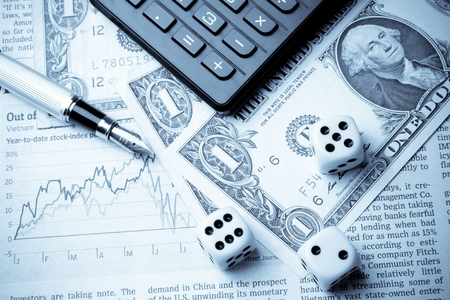 dice on financial chart near dollars and calculator on white table Stock Photo