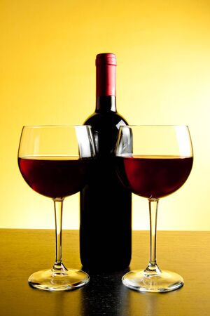 two red wine glasses near bottle on golden background and wood table photo