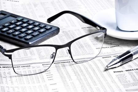 Detail einer Feder und Gläser in der Nähe von einem Rechner mit einer Tasse Kaffee auf Finanzzeitung Standard-Bild - 22668222