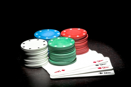 four piles of colorful fiches on a poker aces photo