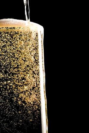 overflow pouring champagne in the flute with golden bubbles on black background and space for text Stock Photo