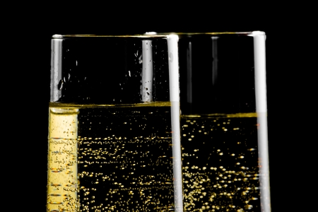detail of a pair of flutes of champagne with golden bubbles on black background
