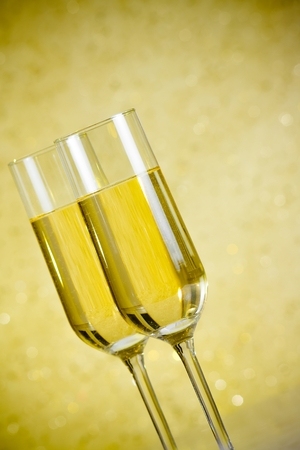 a pair of flutes of champagne on golden bokeh background photo
