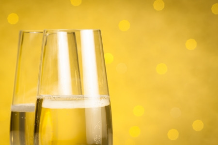 flutes of champagne on golden bokeh background with space for text photo