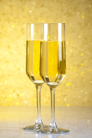 a pair of flutes of champagne on golden bokeh background on table photo