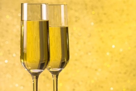 a pair of flutes of champagne on golden bokeh background with space for text photo