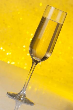 tilted flute of golden champagne on golden bokeh background photo