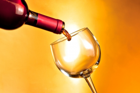 bottle of red wine beginning filling a glass on golden background with space for text photo