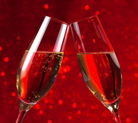 pair of a champagne flutes make cheers on red light bokeh background photo