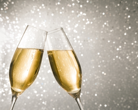 new years eve: champagne flutes with golden bubbles make cheers on silver light bokeh background with space for text