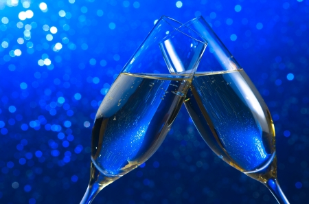 pair of a champagne flutes make cheers on blue light bokeh background with space for text Reklamní fotografie