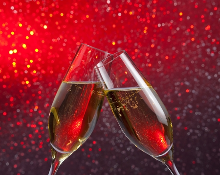 flutes: pair of a champagne flutes with gold bubbles make cheers on red and violet light bokeh background