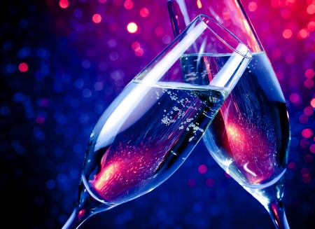 pair of champagne flutes with gold bubbles make cheers on blue tint light bokeh background Stock Photo
