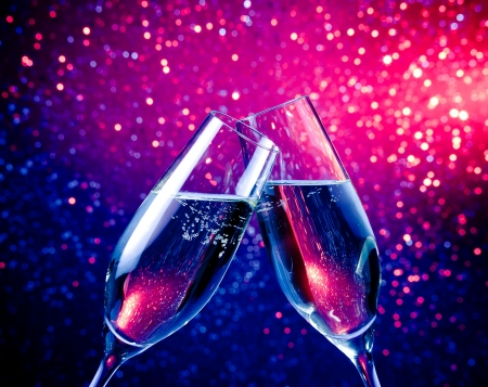 pair of a champagne flutes with bubbles make cheers on blue tint light bokeh background