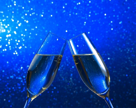 a pair of champagne flutes make cheers on blue light bokeh background with space for text