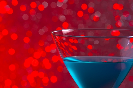 one glass blue cocktail on red tint light bokeh background photo