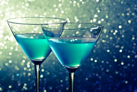 two glasses of blue cocktail on dark green tint light bokeh background on table