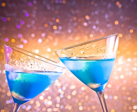 cin: two glasses of fresh blue cocktail with ice make cheers on colorful tint light bokeh with space for text Stock Photo