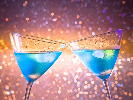 cin: a pair of glasses of fresh blue cocktail with ice make cheers on colorful tint light bokeh with space for text Stock Photo