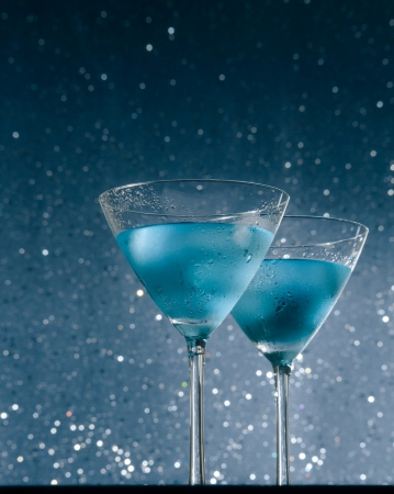 view from below of glasses of fresh cocktail with ice on blue tint light on bar table