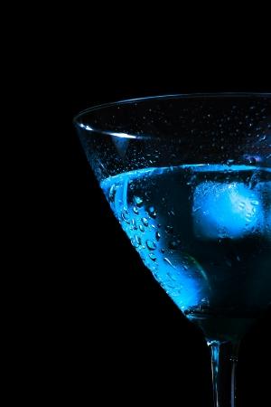 detalj av halvt glas färsk blå cocktail med is på blå nyans ljus och svart bakgrund med utrymme för text