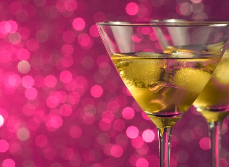 a pair of glasses of fresh cocktail with ice on pink tint light bokeh background with space for text Stock Photo