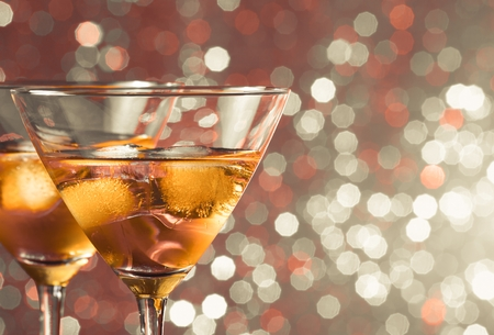 a pair of glasses of fresh cocktail with ice on  light bokeh background with space for text photo