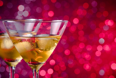 a pair of glasses of fresh cocktail with ice on pink and violet tint light bokeh background with space for text photo