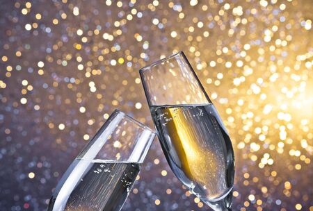 champagne flutes with golden bubbles make cheers on light bokeh background with space for text Stock Photo