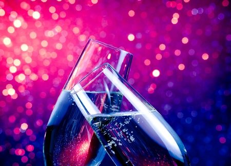 a pair of champagne flutes with gold bubbles make cheers on blue and violet tint light bokeh background with space for text
