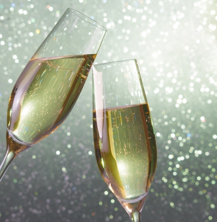 champagne flutes make cheers on silver light bokeh background