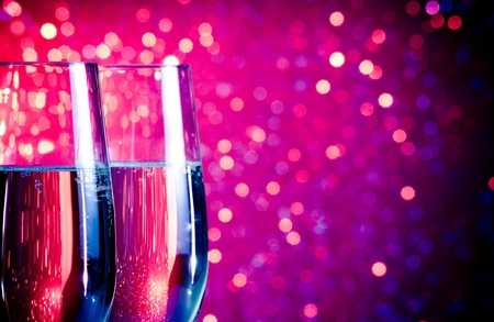 pair of champagne flutes with gold bubbles on blue and violet tint light bokeh background with space for text