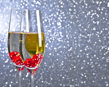 red dice dropping in the champagne flutes on silver tint light bokeh background with space for text Stock Photo