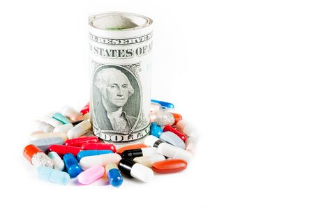 colorful pills near rolled up dollars on white background with space for text photo
