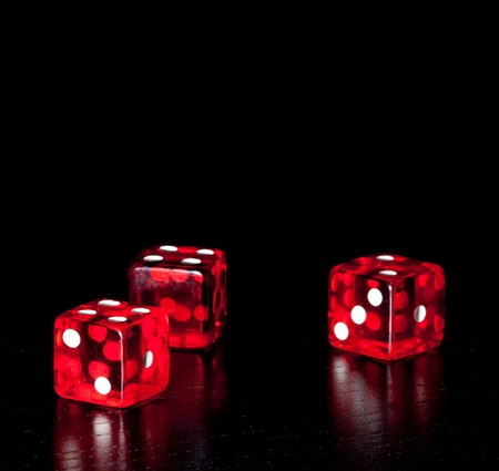 three red dice on old wood black table on black background with space for text