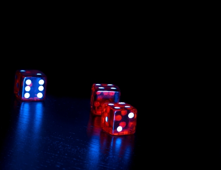 three red dice on old wood black table on light blue tint background with space for text Stock Photo