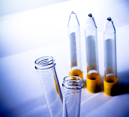reagents: detail of the test tubes in laboratory on table and blue light tint background
