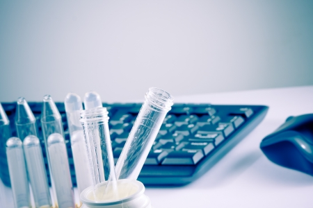 test tubes in laboratory on table near computer keyboard and mouse on table with space for text photo