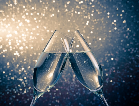 cheers: two champagne flutes with golden bubbles make cheers on blue light bokeh background with space for text