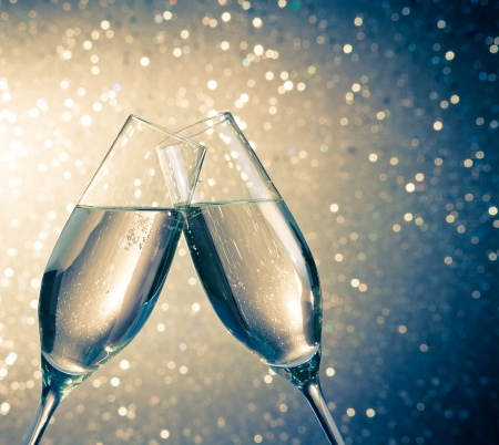 champagne flutes with golden bubbles make cheers on blue light bokeh background with space for text Stock Photo